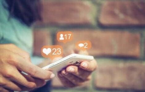 Kan föräldrar kontrollera sina barns sociala medier? händer håller telefon med symboler som svävar ovanför