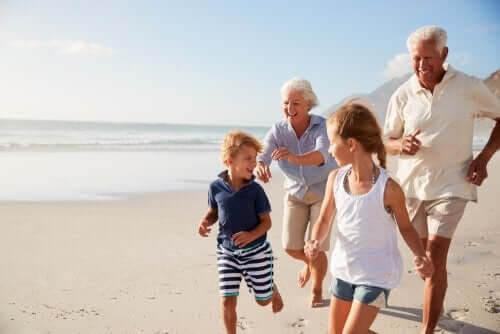 morföräldrar leker med barnbarn på strand
