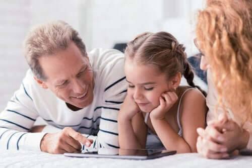uppfostra sina barn: mamma, pappa och dotter tittar i bok tillsammans