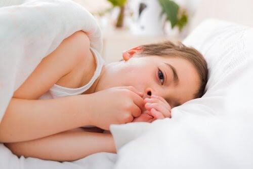 förkylningar: flicka ligger i sängen och ser sjuk ut