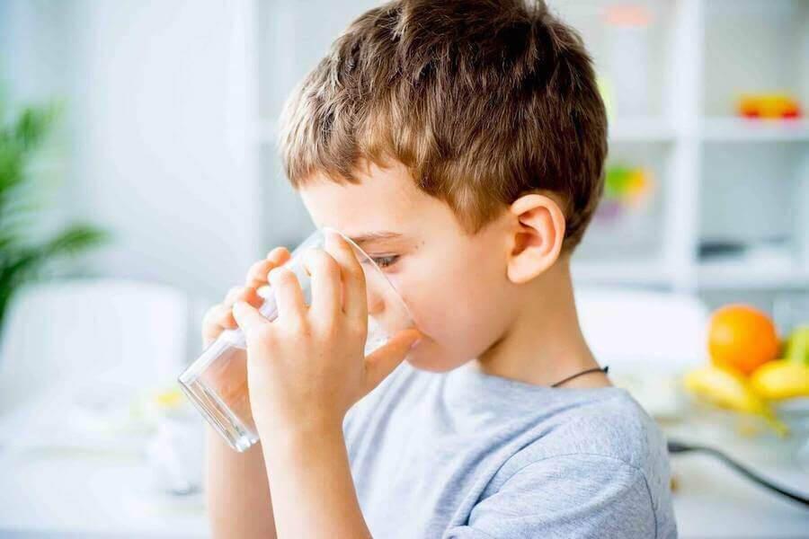 ketos hos barn: pojke dricker ett glas vatten
