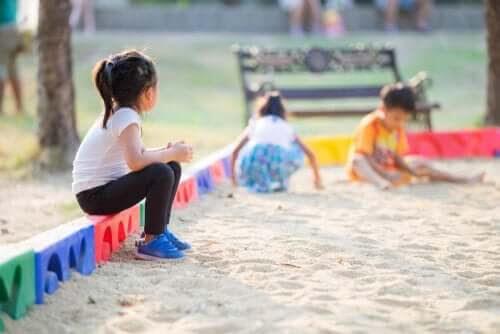 problem med att skaffa vänner: flicka tittar på andra barn som leker
