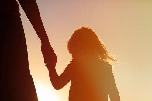 barn håller förälders hand i motljus
