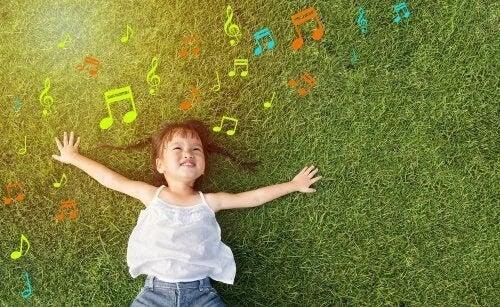 fritidsutbildning: flicka ligger på en äng med noter omkring sig