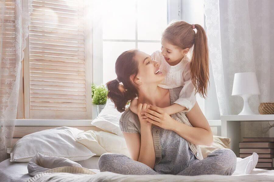 mamma och dotter leker på säng