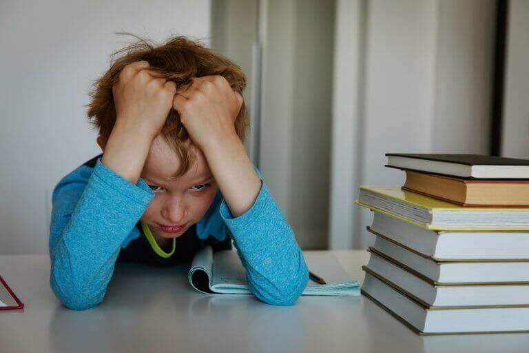 dynamiskt tänkande: frustrerad pojke vid hög med böcker