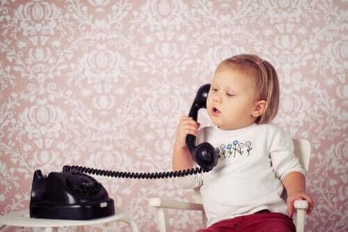 utvecklingen av språk: småbarn leker med telefon