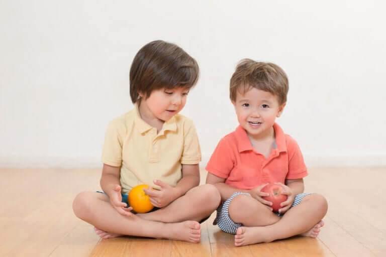 Tvåårstrots: två barn sitter på golvet