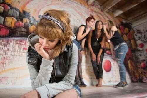 Subkulturer för ungdomar: ung tjej i förgrunden med grupp av ungdommar som viskar i bakgrunden