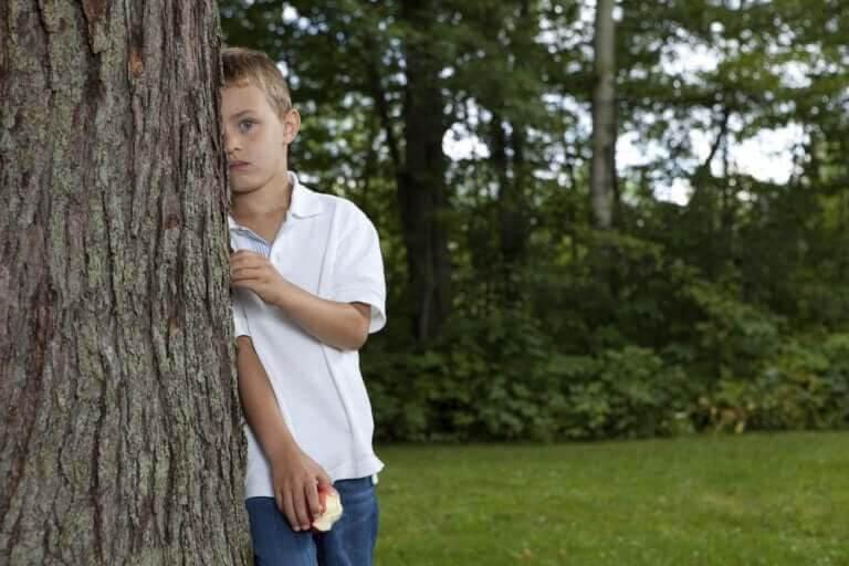 blyga och introverta barn: pojke gömmer sig halvt bakom ett träd