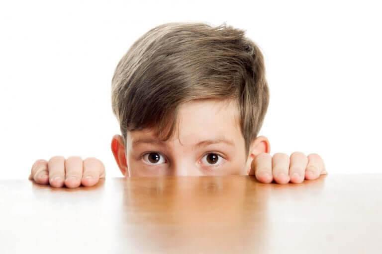 blyga och introverta barn: pojke tittar upp över bordskant