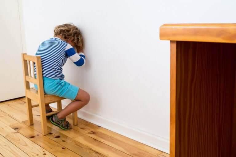 positiva och negativa straff: pojke sitter vänd mot vägg