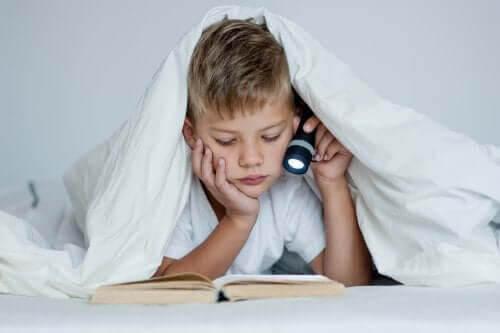 dåliga studievanor: pojke läser med ficklampa