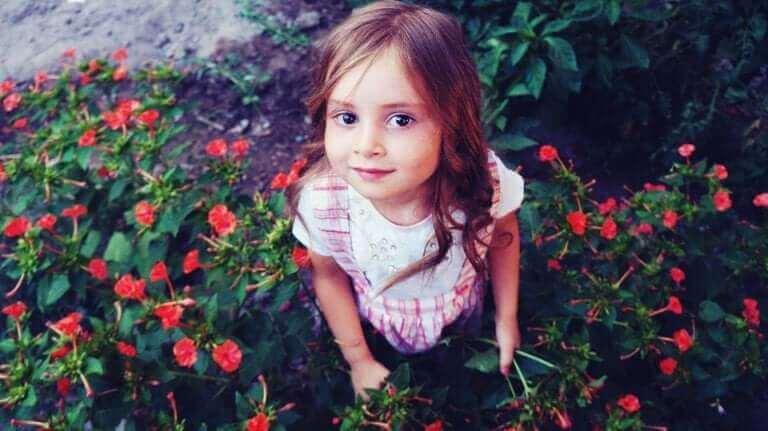 En flicka sitter bland blommor.