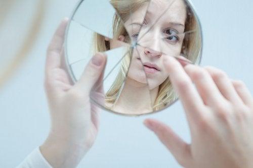 En osäker tonåring tittar i en krossad spegel.