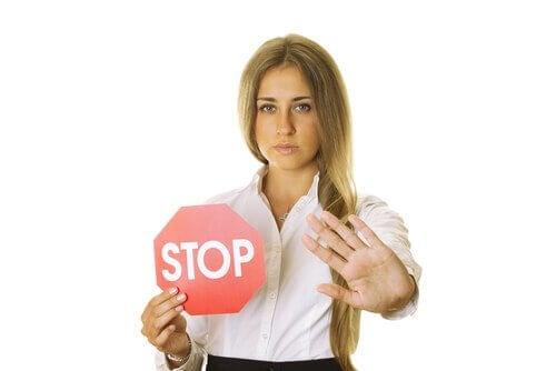 En kvinna sätter gränser med en stoppskylt.