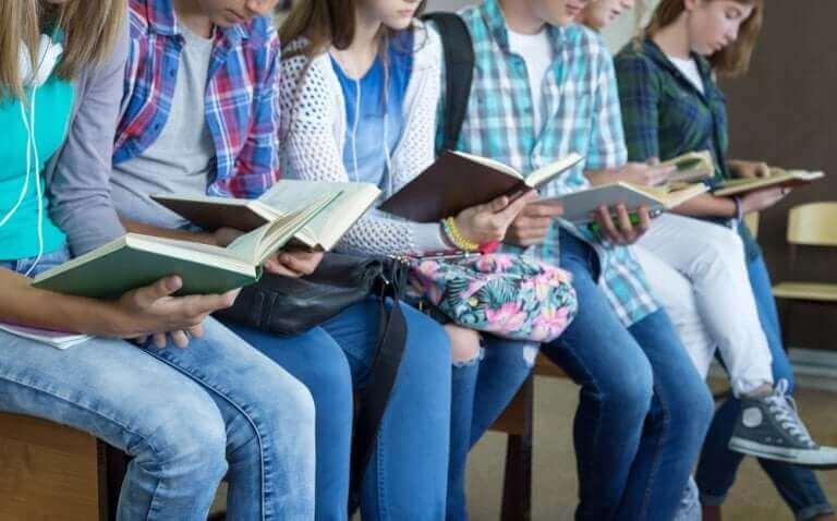 En rad av tonåringar som läser.