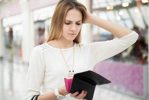 Tonåring tittar förbryllad på pengar i plånbok