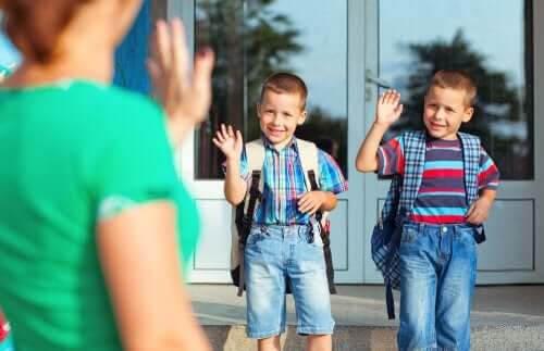 Barnkonventionen: barn vinkar hejdå till mamma utanför skola