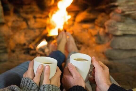 man och kvinna framför öppen eld med muggar