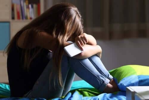 ledsen tonåring med telefon