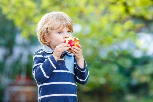 Ett barn som äter ett äpple.