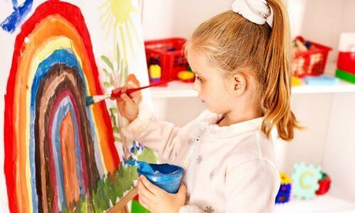 Ett barn som målar en regnbåge.