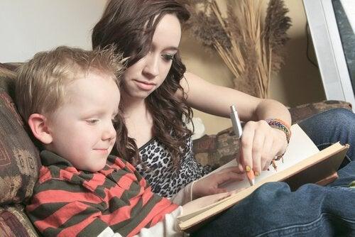 Barnflicka hjälper pojke med skoluppgifter