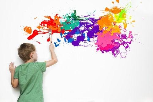 Ett särbegåvat barn målar på väggen.