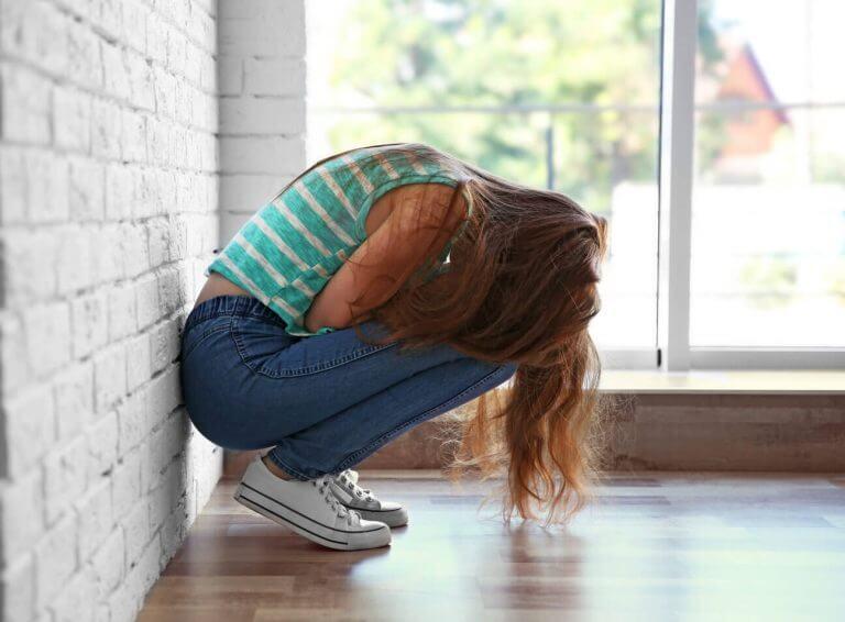 Bli av med bitterhet: en tonårsflicka som sitter ihopkrupen.