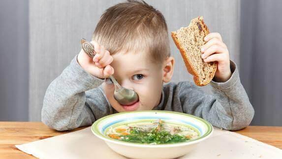 Ett barn äter hälsosam soppa.