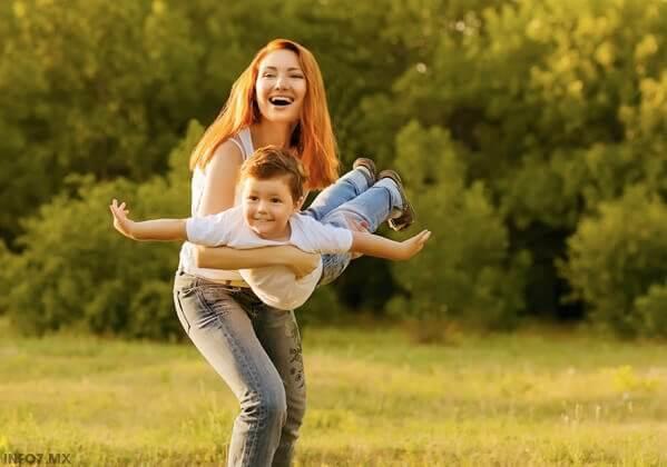En mamma leker flygplan med sin son.
