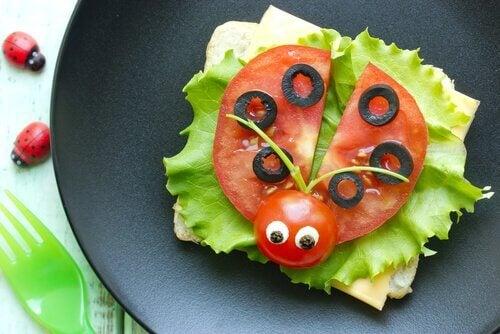 En smörgås med grönsaker i form av en nyckelpiga.