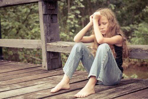 En sorgsen flicka som sitter ner.