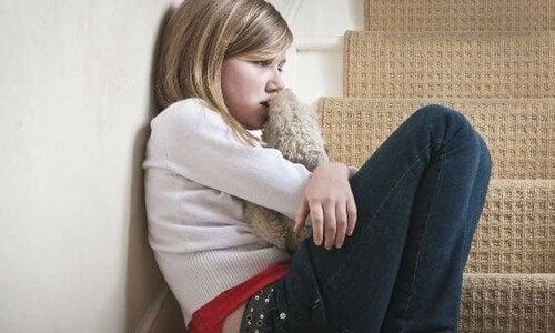 Ett sorgset barn sitter i en trappa.