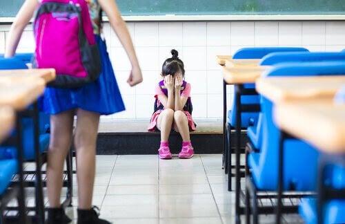 säkerhetsregler: ledsen flicka på golvet i klassrum