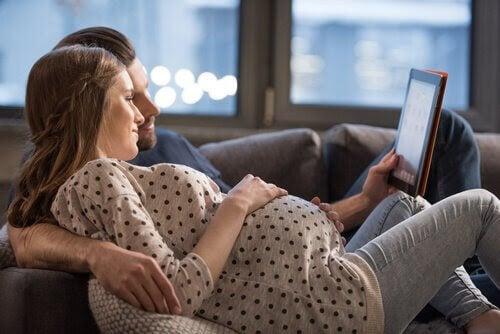 man och gravid kvinna i soffa tittar på läsplatta