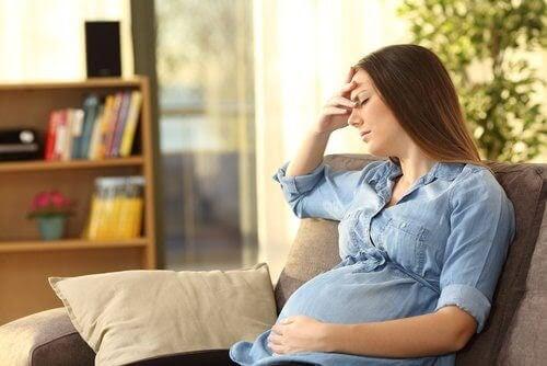 gravid kvinna oroar sig i soffa