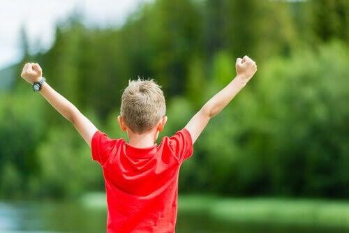 självuppfattning: pojke med armarna i segergest