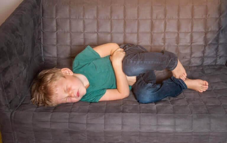 Stolpiller: barn med magvärk ligger på soffa