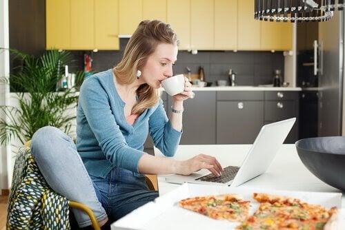 mamma med laptop i kök med pizza