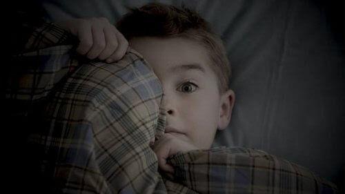 rädda för att vara ensamma: rädd pojke i säng