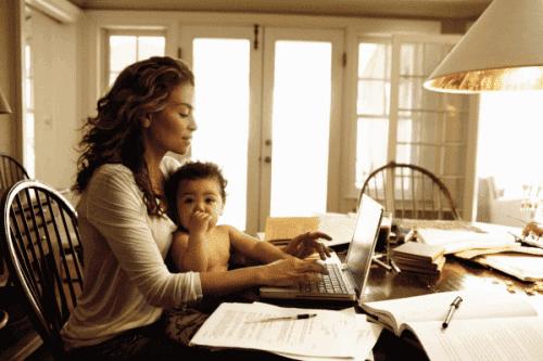mödrar som arbetar hemifrån: mamma vid dator med baby i famnen