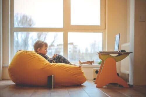 Ett barn sitter i en sittsäck och ser på tv.