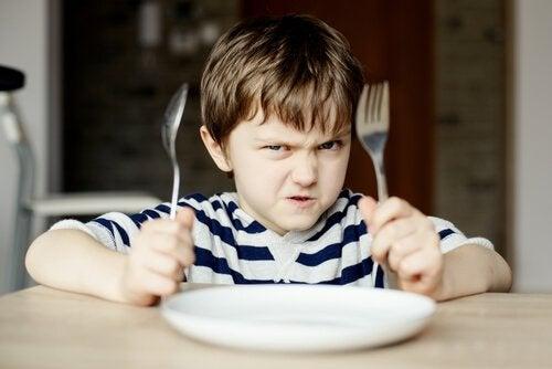 Argt barn med tom tallrik