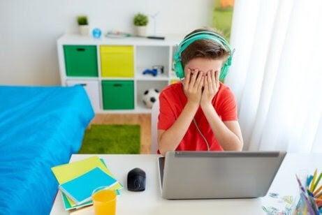 negativa effekterna av teknologi: pojke håller för ögonen framför dator