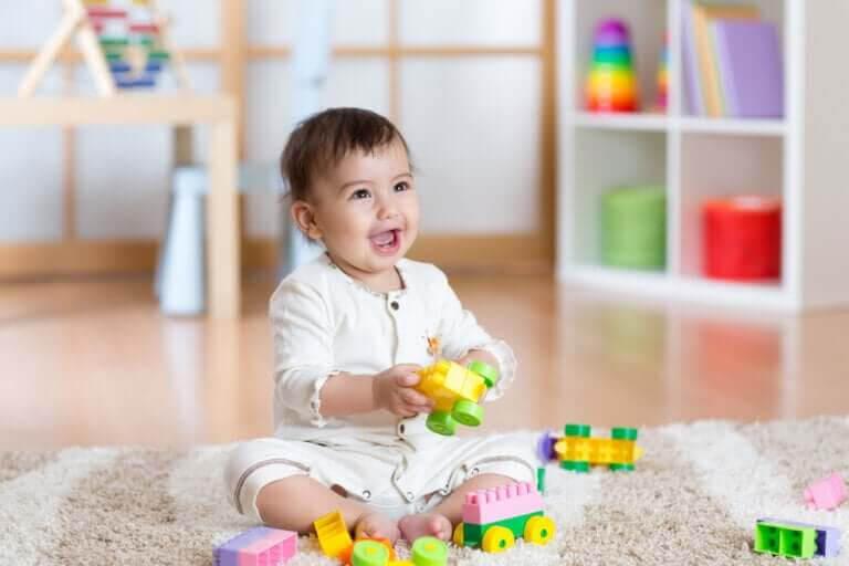 barns motoriska färdigheter: baby leker med leksaker