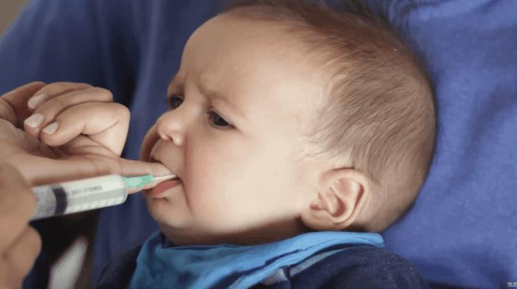 Tuttförvirring: baby suger på finger med matningsslang
