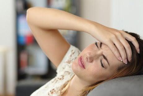 symptomen under den första trimestern av graviditeten: kvinna håller sig för pannan