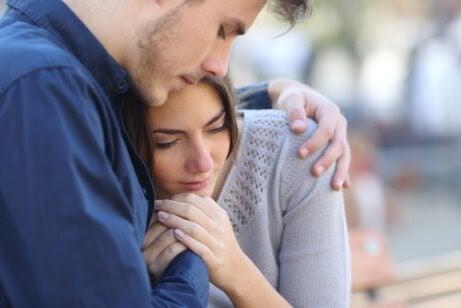 symptomen under den första trimestern av graviditeten: man kramar kvinna